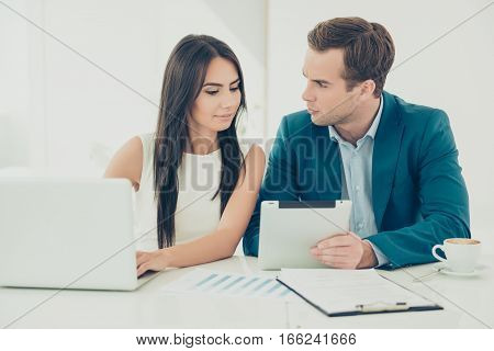 Portrait Of Two Colleagues In Formal Wear Working On Project And Using Laptop And Tablet
