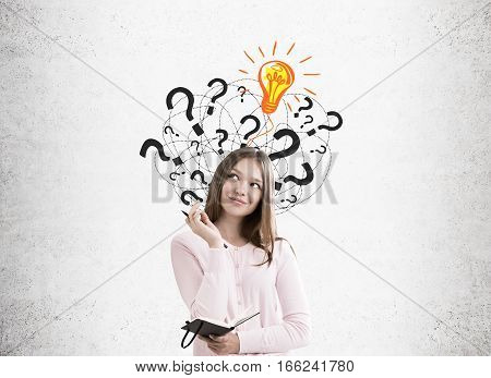 Portrait of a young woman holding a notebook and a pen and standing near a concrete wall with light bulb and question marks.