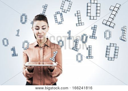 Portrait of a woman looking at her tablet computer and standing near a white wall with a ones and zeros flying around her.