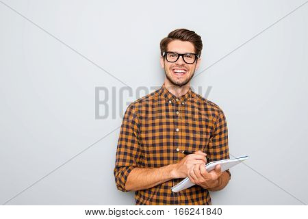 Happy Young Smart Student In Glasses Writing In Notebook