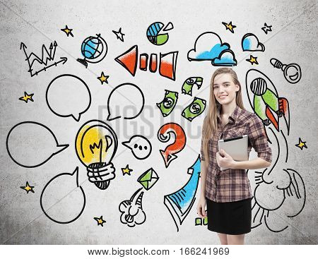 Portrait of a girl with a tablet wearing a checkered shirt who is standing near a concrete wall with colorful start up icons drawn on it.