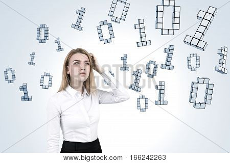 Portrait of a blond woman scratching her head and standing near a white wall with a ones and zeros flying around her.