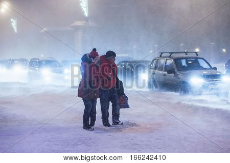 ARKHANGELSK, RUSSIA - JANUARY 22, 2017: Man and woman cross road at heavy night winter snowstorm. Low visibility, street traffic. Concept bad winter weather.