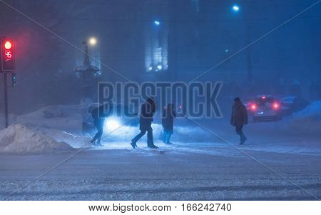 People cross road at heavy night winter snowstorm. Low visibility, street traffic. Very cold snowy weather.