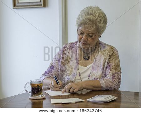 Mature woman writing a letter with an ink pen at table with tea mug and thank you notes