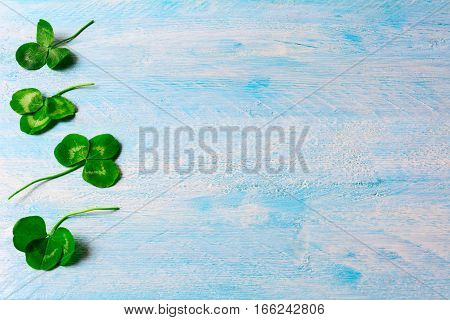 St. Patricks day greeting card with shamrock. Border of Clovers leaves on blue wooden background. Copy space.