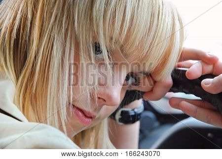 Blonde girl thinking behind the wheel of a car