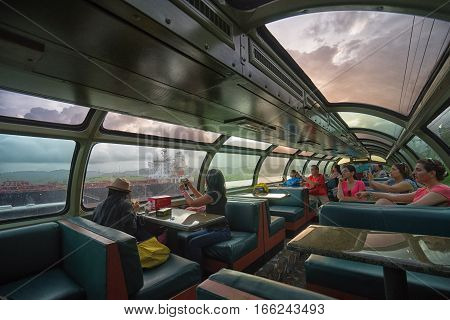 June 28, 2016 Colon, Panama: the interior of Panama Railway train commuting the capital city with Colon with tourists taking photos of a ship crossing the canal