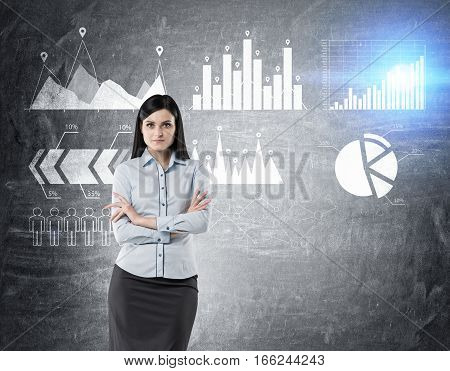 Portrait of a woman in a blue shirt standing with her arms crossed near a blackboard with six graphs. Toned image.
