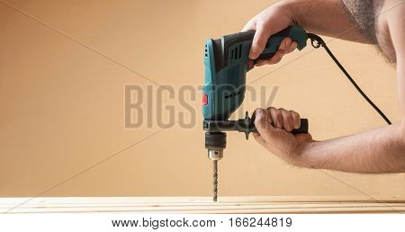 Man with green drill grilling hole on lining woods. Yellow orange copy space wall