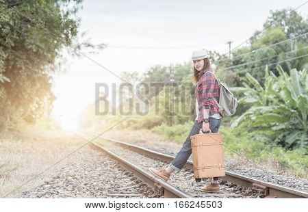 Hipster young girl with backpack walk on railway on vintage tone concept travel and recreation