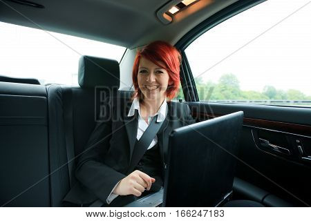 a young businesswoman is sitting in her car, looking at the camera