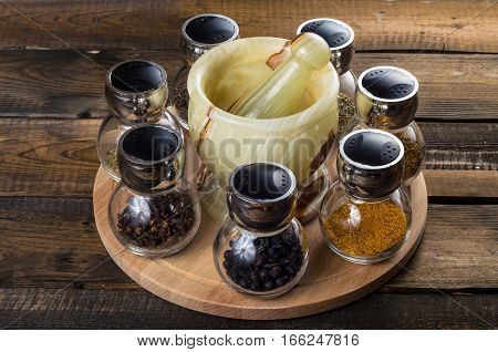 spices in spoons and Jar with mortar on a wodeen background