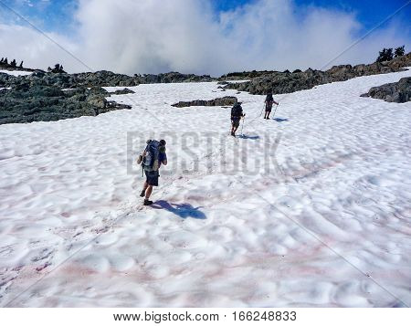 Hikers Traverse Snowy Moonscape in Alpine Terrain