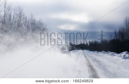 The car when overtaking has lifted a loop of snow dust. Poor visibility. Danger on road concept.