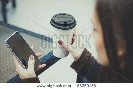 Cafe city lifestyle young woman texting message and drinking coffee sitting indoor in trendy urban cafe.