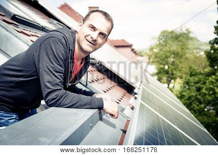 this home owner is happy with the solar panels on his roof. he saves a lot of money by generating his own electricity.
