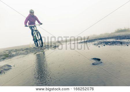 Photo of Mountain Biker Racing Through Puddle