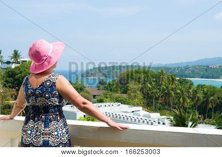Woman enjoying the view over Kata beach from the hotel balcony. Phuket, Thailand