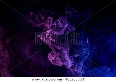 Abstract smoke Weipa. Personal vaporizers fragrant steam. The concept of alternative non-nicotine smoking. Blue lilac smoke on a black background. E-cigarette. Evaporator. Taking Close-up. Vaping.
