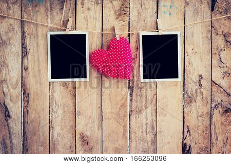Red Heart And Two Photo Frame Hanging On Clothesline Rope With Wooden Background.