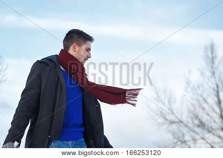 Man walking with a bottle of wine. He is dressed in winter coat scarf and gloves. Man in Profile