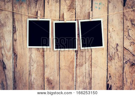 Three Photo Frame Hanging On Clothesline And Rope With Wooden Background.