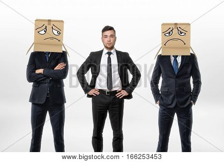 One businessman standing between two other men wearing carton boxes with drawn sad faces on them. Business and work. Fitting in. Workplace communication.