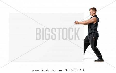 Muscular man holding a clear white display board with his fists. Sports and fitness. Fitness industry. Promotion and ads.