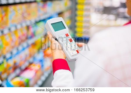 Young female sales clerk working at the supermarket