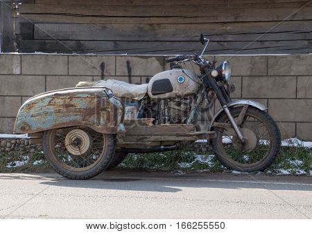 A vintage motorcycle with rusted and  peeling paint and in disrepair parked in front of a block fence. The rear has a platform and two wheels.