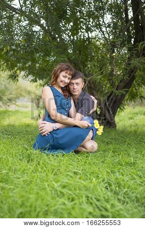 Lovers Man And Woman Sitting In The Shade Of A Leafy Tree.