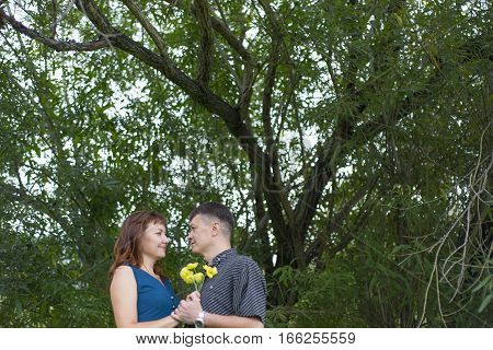 Lovers Man And Woman Stand In The Shade Of A Leafy Tree.