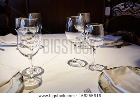Empty glasses in a restaurant on a white tablecloth.