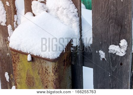 Snow on the mailbox hanging on wooden fence