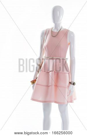 Dress and accessories on mannequin. Female mannequin in evening outfit. Salmon dress with white belt. Mannequin on shop's showcase.