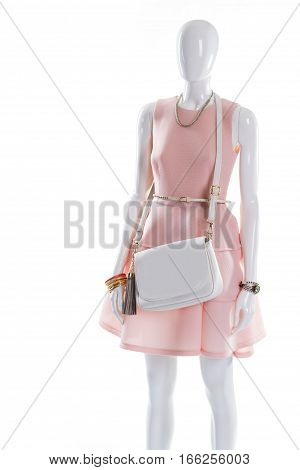 Dress and purse on mannequin. Elegant outfit on female mannequin. White dress belt and purse. Gilded bracelet and leather handbag.
