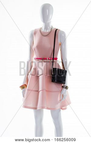 Dress with accessories on mannequin. Female mannequin in fashionable clothing. Evening outfit with retro handbag. Dress with belts and accessories.