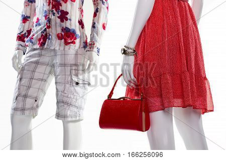 Shorts and sarafan on mannequins. Mannequins in stylish clothing. Lady's purse and man's shorts. Female accessories and men's apparel.