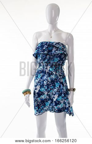 Dress with jewelry on mannequin. Female mannequin in floral dress. Flower pattern dress and accessories. Woman's summer garment on sale.