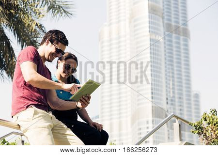 tourists to dubai writing an email on their digital tablet computer.