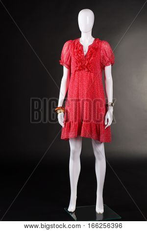 Red v-neck dress and accessories. Mannequin wearing red summer dress. Colorful garment on black background. Woman's brand new stylish apparel.