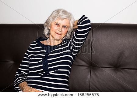 A senior woman showing that she enjoys retirement by relaxing.