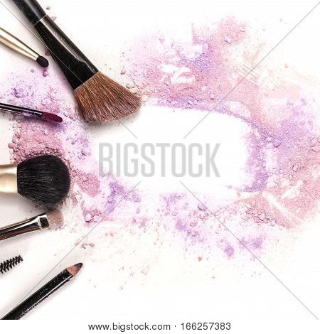 Makeup brushes, lip gloss and pencil on white background, with traces of powder and blush forming a frame. A square template for a makeup artist's business card or flyer design, with copyspace poster