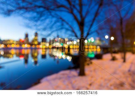 Portland Oregon downtown skyline along Willamette River during winter blue hour blurred defocused bokeh