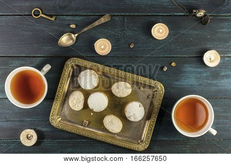 A photo of mantecados and polvorones, traditional Spanish cookies, shot from above on a vintage tray with a cup of tea and candles on a dark wooden background, with copyspace