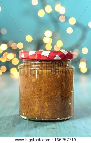 A photo of a jar of fruit butter on a blurred festive background with copyspace