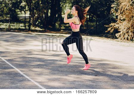sports girl in the park performing various exercises. uses communication