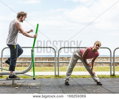 Active young man exercising on elliptical trainer machine and woman stretching. Muscular sporty guy and girl in training suit working out at outdoor gym. Sport fitness and healthy lifestyle concept.