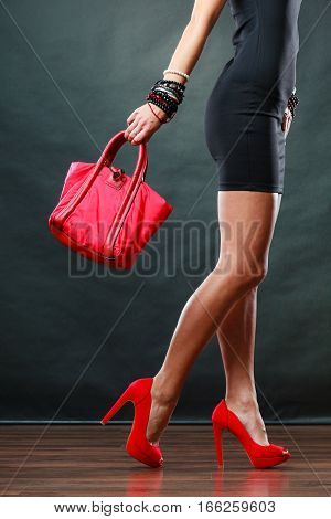 Celebration evening fashion concept. Woman in black short dress red spiked shoes holding handbag bag female legs in high heels on party floor